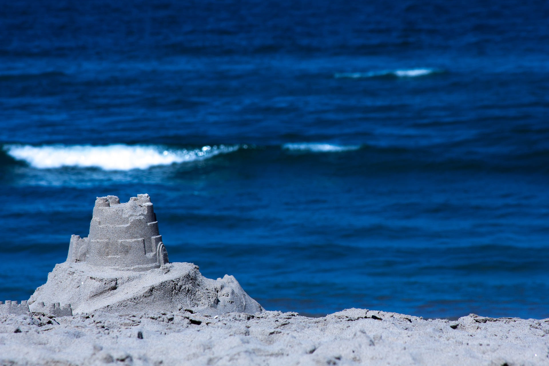 A single round sand castle with blue ocean in the background