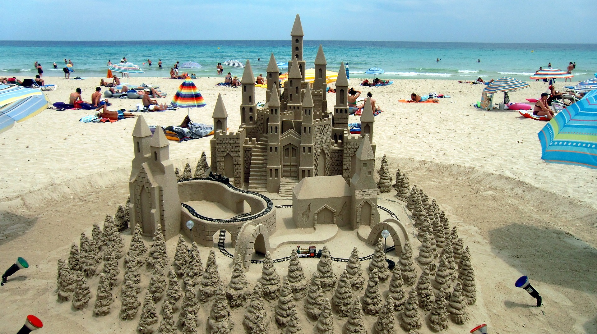 A sand castle with towers and a train track and sand trees