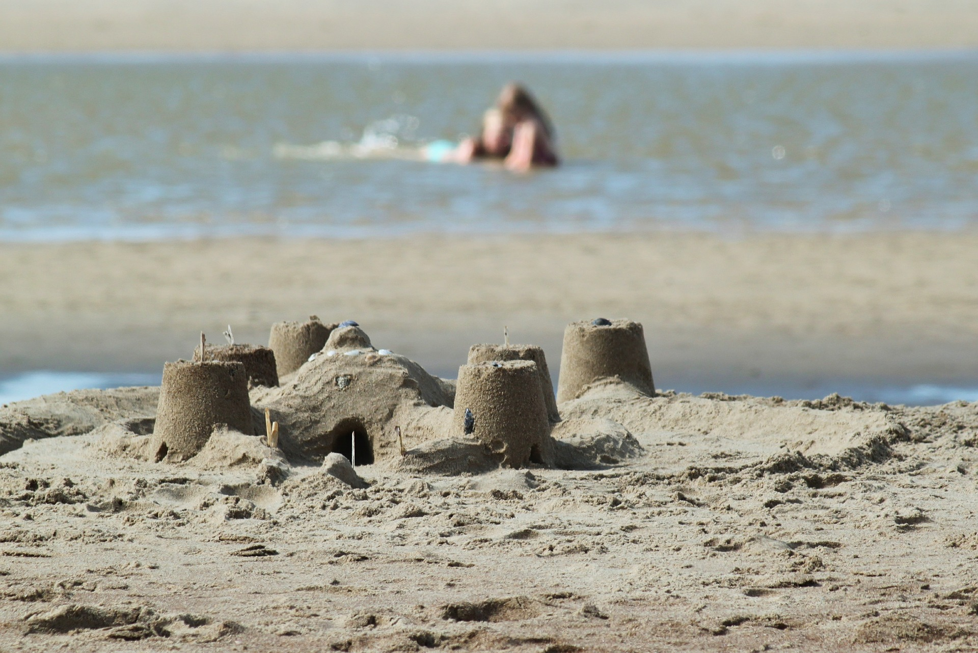 A simple sand castle with water in the background